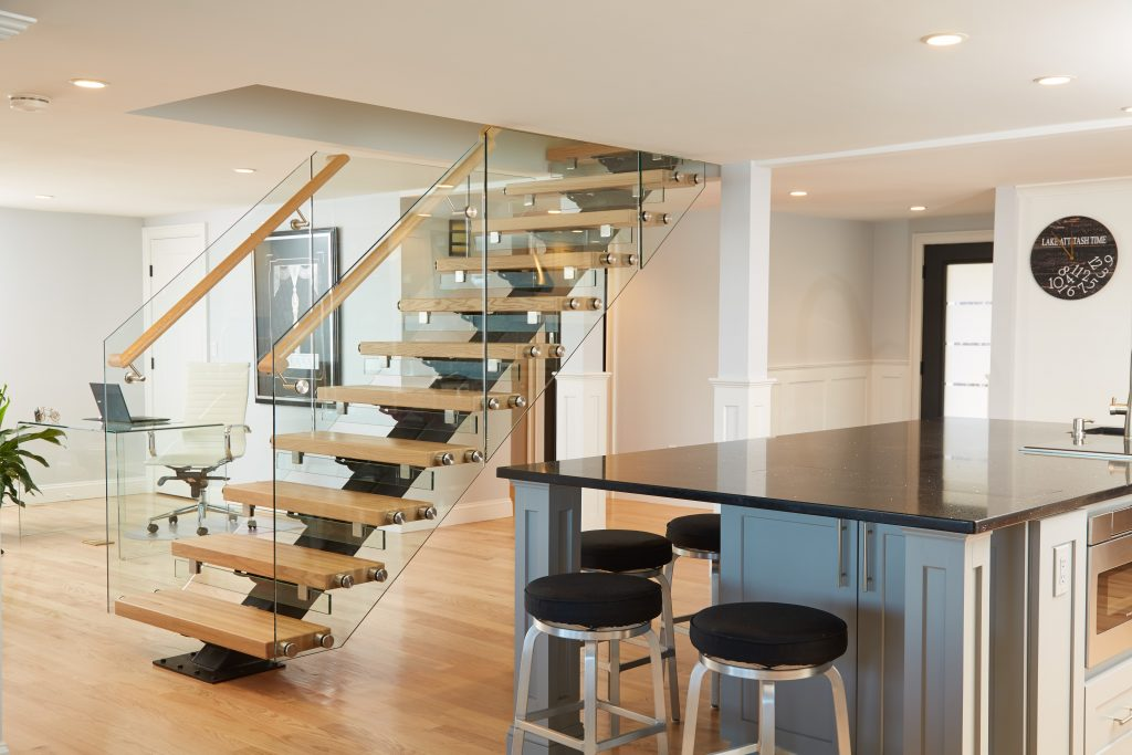 Glass railing panels with hand rail on floating stairs